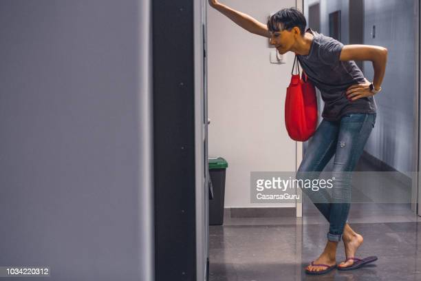 mid adult woman choosing products from vending machine - vending machine stock photos and pictures