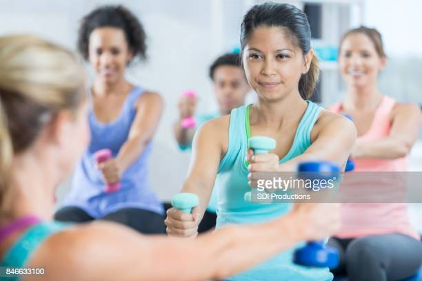 Mid adult woman concentrates during exercise class