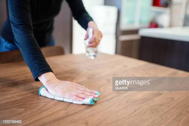 家庭内のダイニングテーブルを消毒する中期成人女性 - 片付いた部屋 ストックフォトと画像