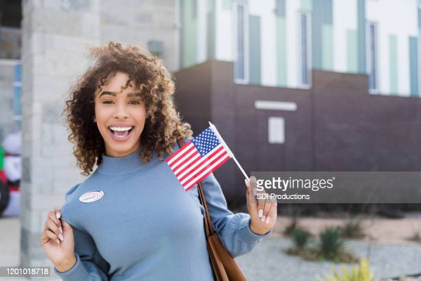 "mid adult woman displays ""i voted"" sticker and american flag - citizenship stock pictures, royalty-free photos & images"