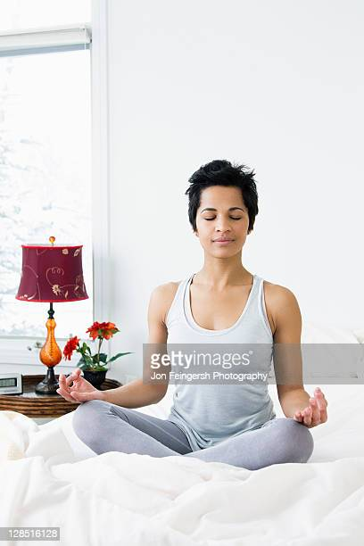 Mid adult woman doing siddhasana on the bed