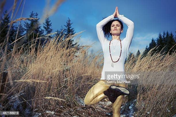 Mid adult woman doing standing tree yoga pose in forest