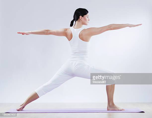 Mid adult woman doing yoga against white background