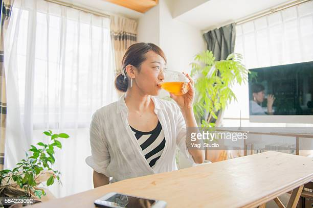 Mid adult woman drinking beer at home
