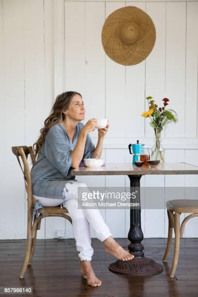 mid adult woman drinking coffee by herself - comida flores fotografías e imágenes de stock
