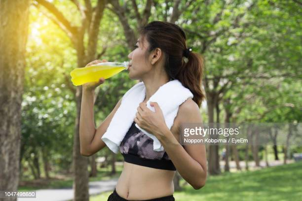 mid adult woman drinking energy drink in park - energy drink stock pictures, royalty-free photos & images