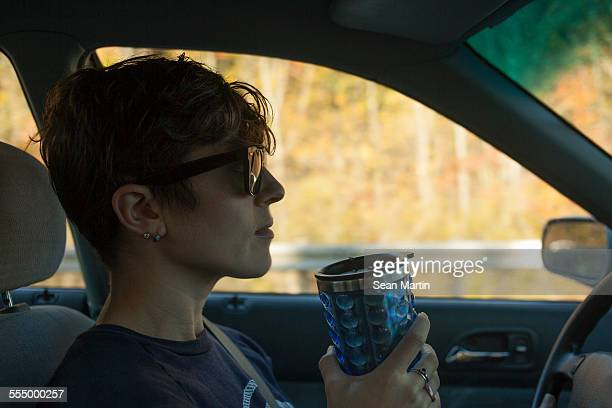 Mid adult woman drinking from flask whilst driving car