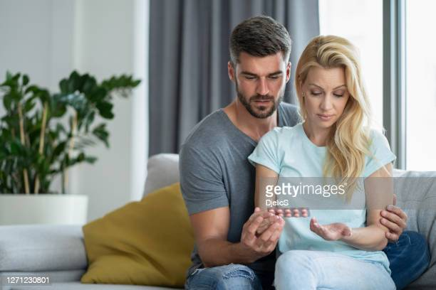mid adult woman drinking pills. - contraceptive stock pictures, royalty-free photos & images