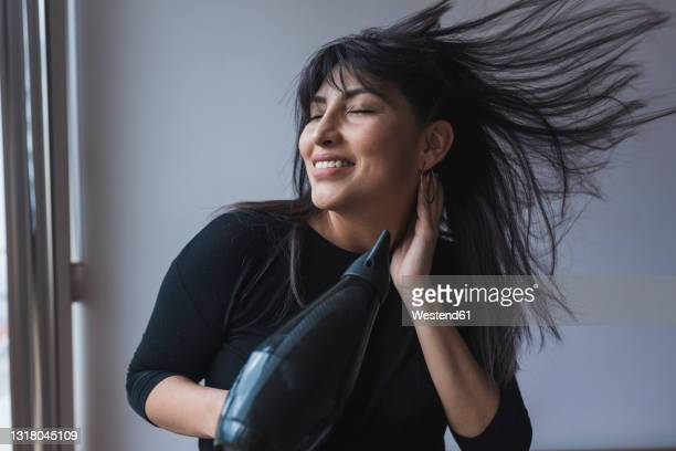 mid adult woman drying hair through hair dryer at home - blow drying hair stock pictures, royalty-free photos & images