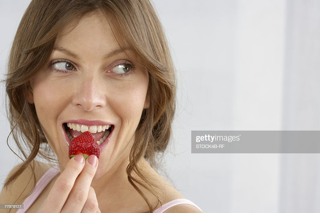 Mid adult woman eating a strawberry : Photo