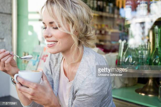 Mid adult woman eating froth from coffee cup at city sidewalk cafe