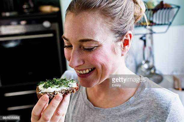 Mid adult woman eating rye bread snack in kitchen