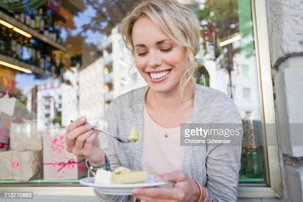 Mid adult woman eating slice of cake at city sidewalk cafe