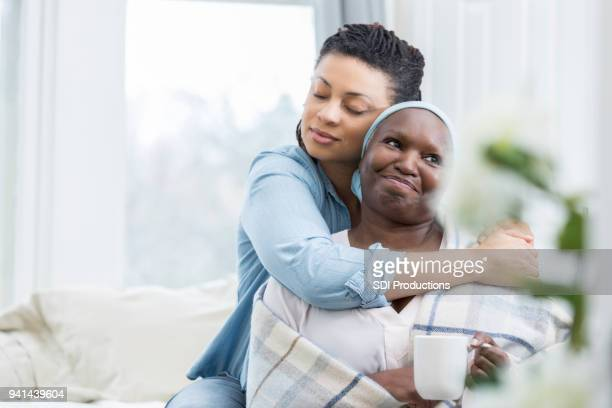 mid adult woman embraces her senior mom - visita imagens e fotografias de stock