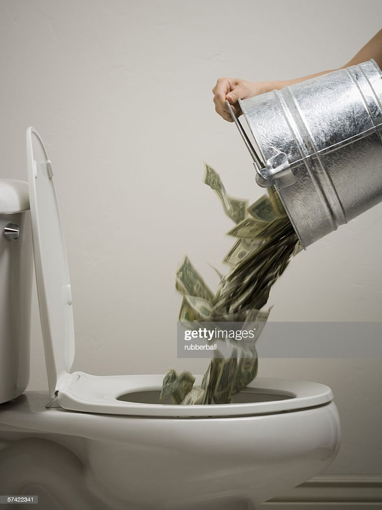 Mid adult woman emptying a bucket of money into a toilet bowl : Stock Photo