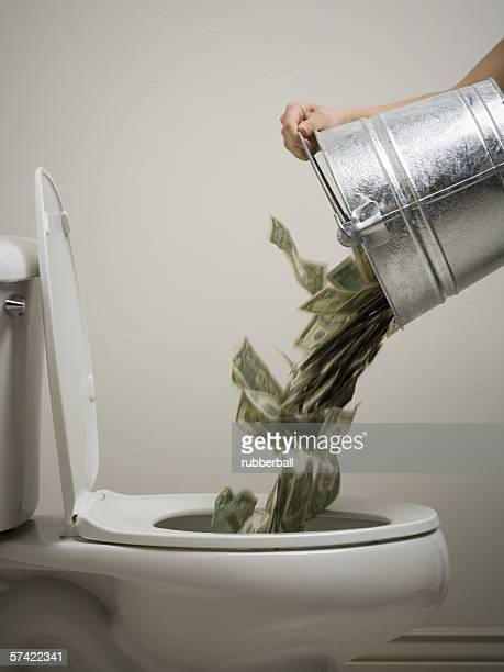 Mid adult woman emptying a bucket of money into a toilet bowl