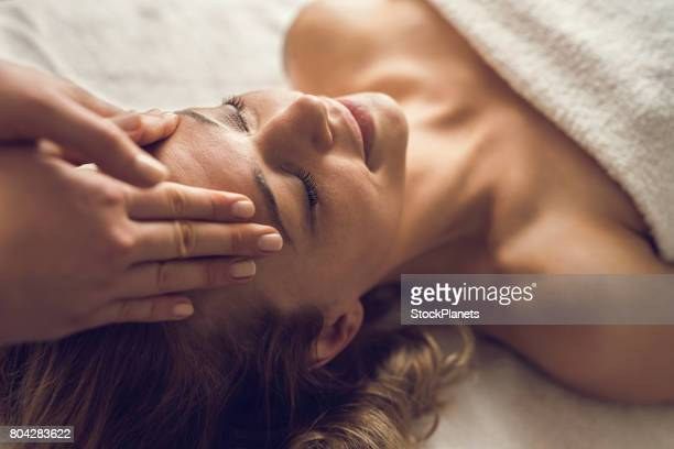 mid adult woman enjoying in her relaxing head massage at the spa. - massage therapist stock pictures, royalty-free photos & images