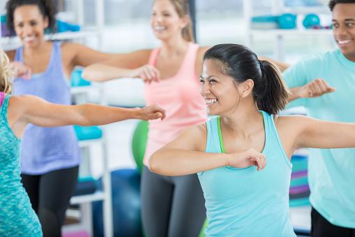 Mid adult woman enjoys aerobics class 811106430