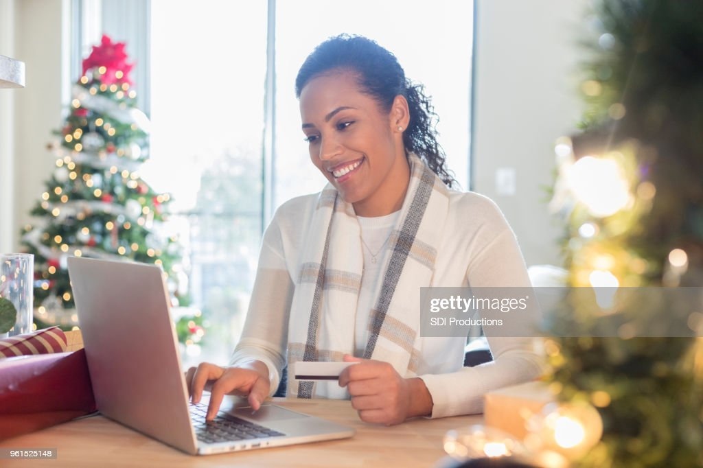 Mid adult woman enjoys Christmas shopping online from home : Stock Photo