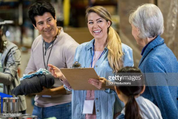 mid adult woman enjoys leading food bank volunteers - charity benefit stock pictures, royalty-free photos & images