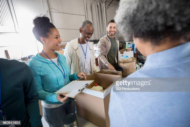 mid adult woman enjoys organizing food bank donations - volunteer stock pictures, royalty-free photos & images