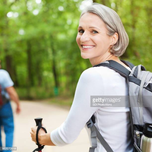 mid adult woman enjoys outdoor hiking trail - mid adult women stock pictures, royalty-free photos & images