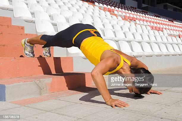 Mid adult woman exercising on stadium
