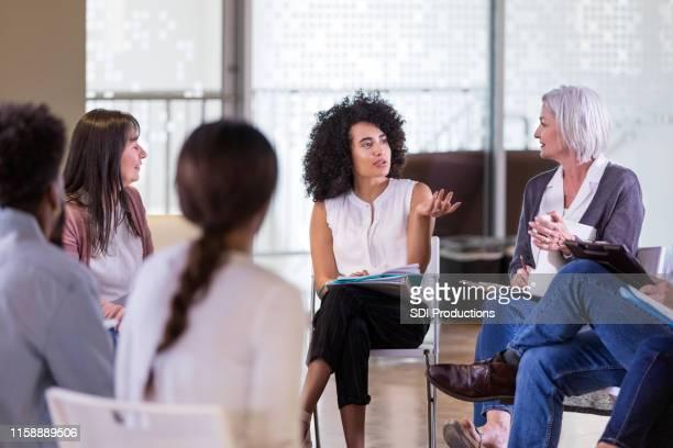 a mulher adulta meados de explica seu problema durante a sessão da terapia do grupo - movimento - fotografias e filmes do acervo