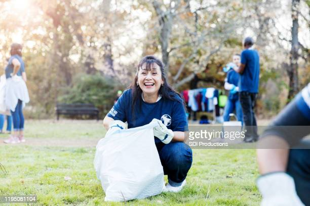 mid adult woman finishes filling bag at cleanup event - selfless stock pictures, royalty-free photos & images