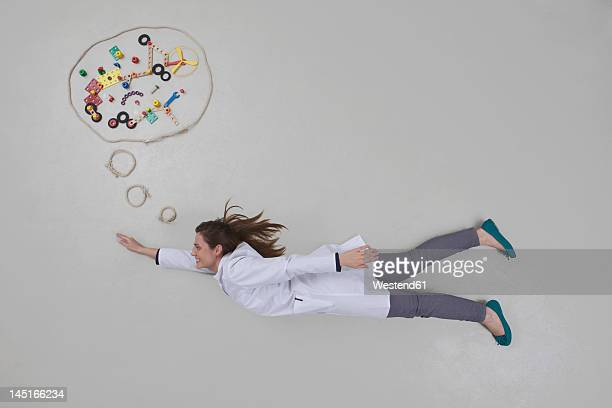 Mid adult woman flying and thinking, smiling