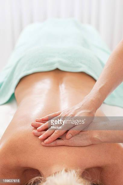 Mid adult woman getting a back massage from mature masseur at health spa