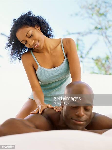 mid adult woman giving a back massage to a man - tantra massage stock-fotos und bilder