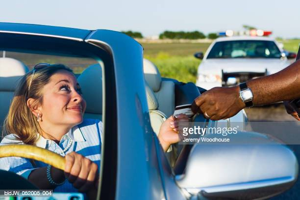 Mid adult woman giving her driver's license to a police officer