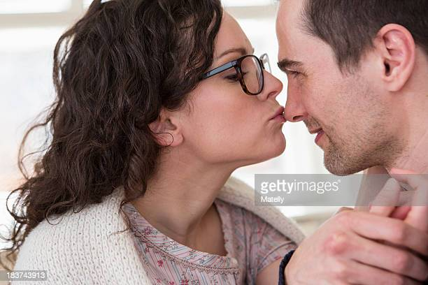 Mid adult woman giving man a kiss on the nose