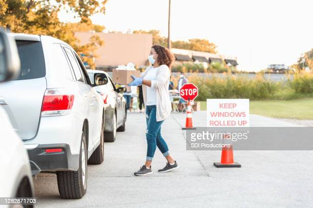 mid adult woman hands food to person sitting in vehicle - drive through stock pictures, royalty-free photos & images