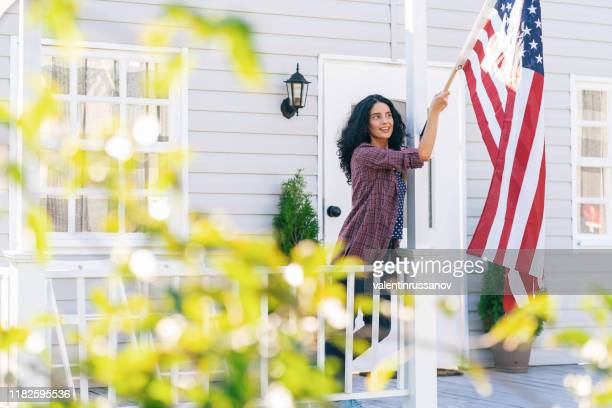 mid adult woman hangs a american flag on her porch and celebrating fourth of july - national holiday stock pictures, royalty-free photos & images
