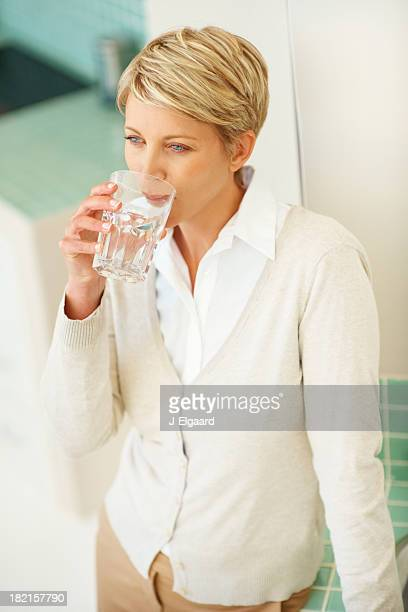 Mid adult woman having a glass of water