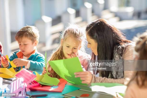 mid adult woman helping children with crafting activity - basteln stock-fotos und bilder