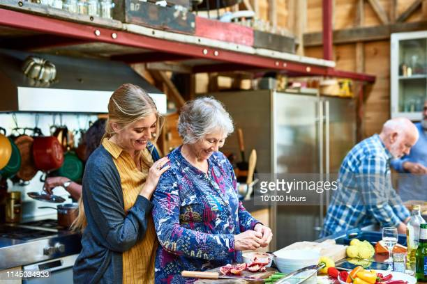 mid adult woman helping her mother make dinner at home - cooked stock pictures, royalty-free photos & images