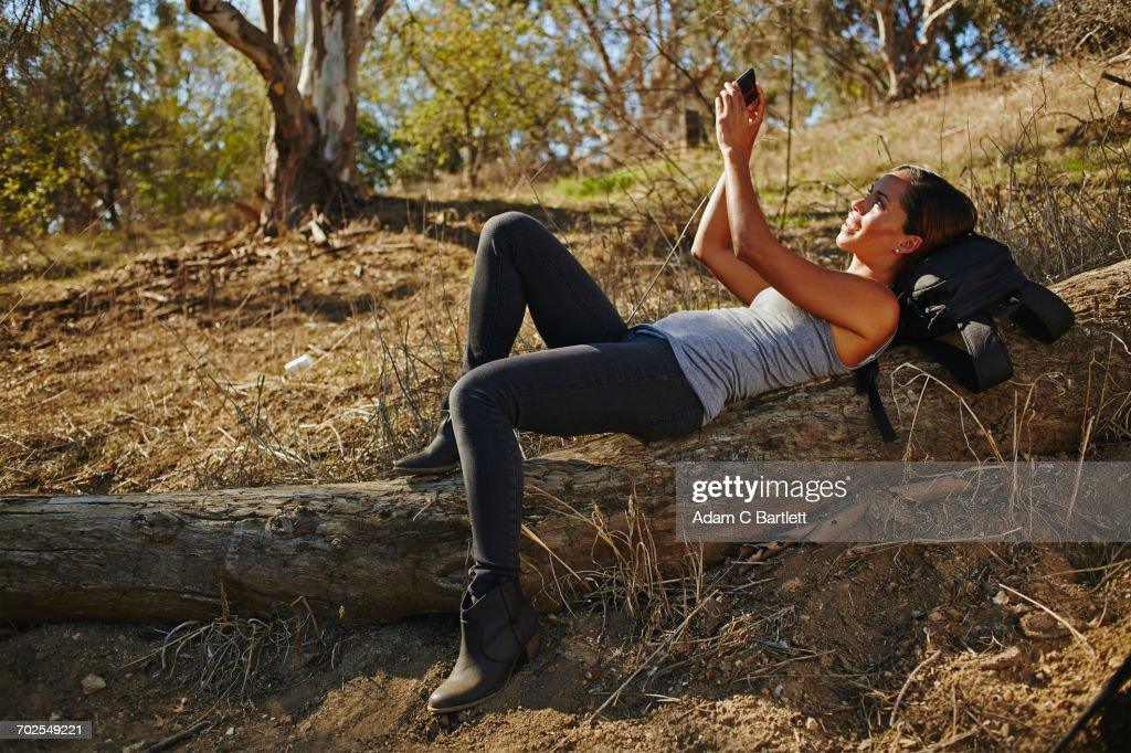 Mid Adult Woman Hiking Reclining On Log Taking Smartphone