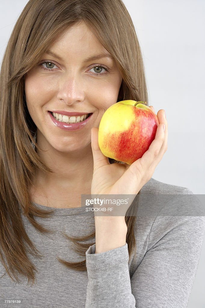 Mid adult woman holding an apple : Stock Photo