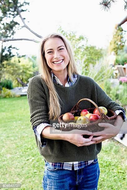 Mid adult woman holding basket of apples, portrait