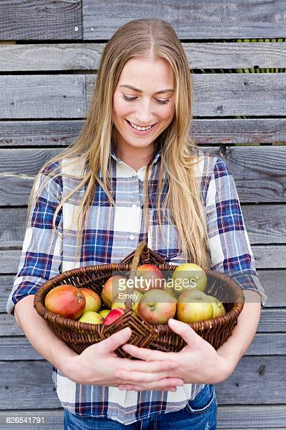 Mid adult woman holding basket of homegrown apples