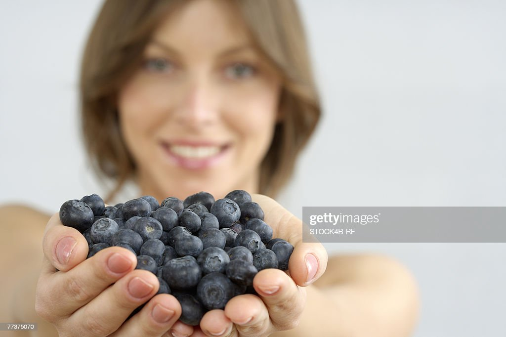 Mid adult woman holding blueberries : Photo