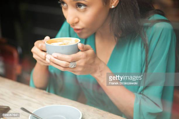 Mid adult woman holding coffee cup looking out of cafe window