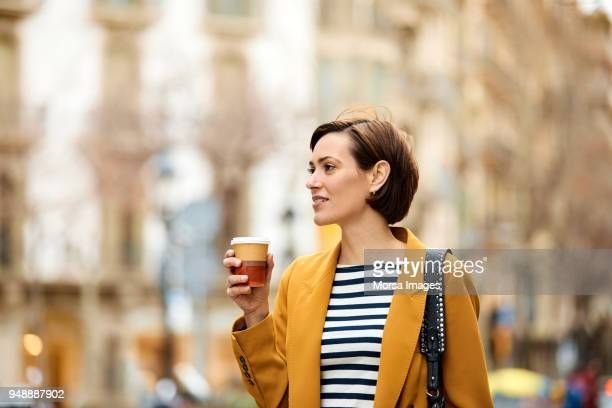 mid adult woman holding disposable cup in city - disposable cup stock pictures, royalty-free photos & images