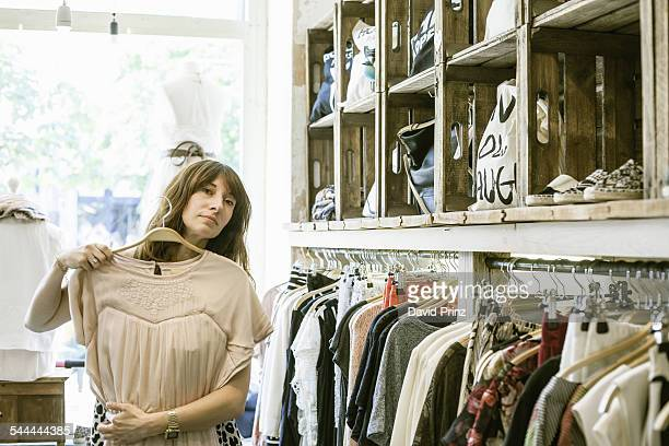 Mid adult woman holding dress in front of herself in vintage boutique