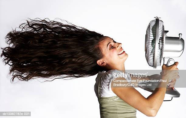 Mid adult woman holding electric fan in front of face, side view