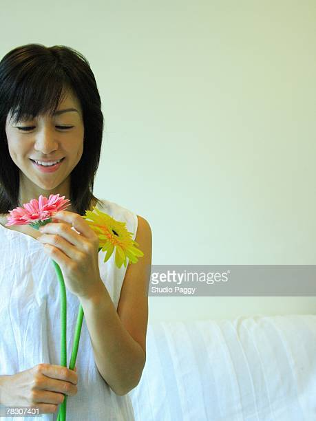mid adult woman holding gerbera daisy flowers and smiling - ミディアムヘア ストックフォトと画像
