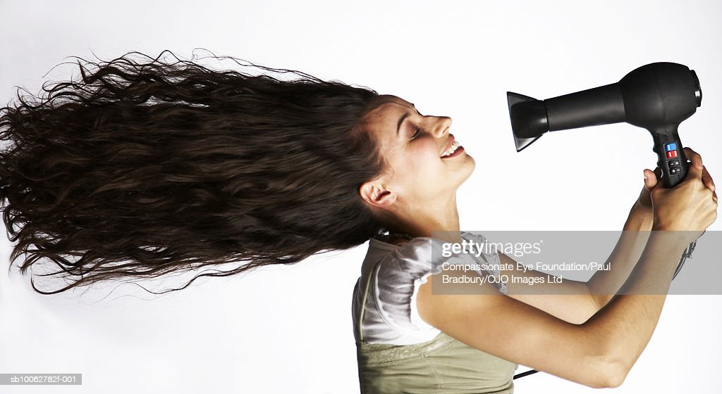 Mid Adult Woman Holding Hair Dryer In Front Of Face Side View Foto